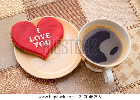 Romantic breakfast concept with coffee, tulips and heart-shaped gingerbread