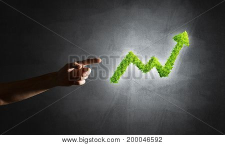 Close of businessman hand and green growing graph as symbol of progress and income