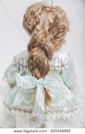 Back view of ceramic porcelain handmade vintage doll with long blond hair and elegant pigtail hairstyle with light green bow in old linen dress with floral decorative embroidery on white background. poster