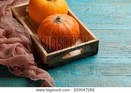 Photo of two orange pumpkins on wooden box on blue surface, blank space for recording