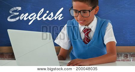 Schoolboy using laptop at table against blue wall over brick wall
