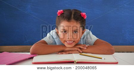 Girl clenching teeth while leaning on book against bueboard on brick wall