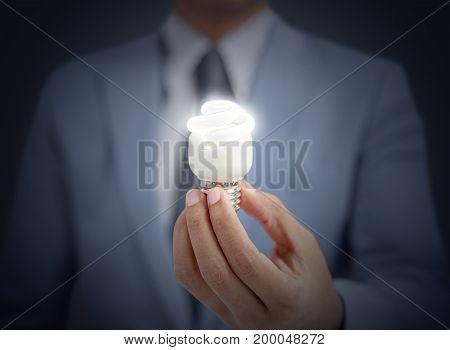 businessman holding light bulb on black background
