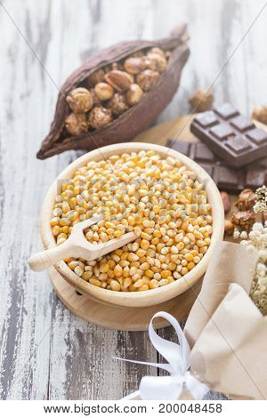 Corn Kernels In Wooden Plates And Popcorn With Caramel And Chocolate Cream On Wooden Table