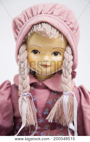 Portrait of a ceramic porcelain handmade vintage doll with yellow face and two pigtails in an old textile knitted pink dress with print in big hat on white background.
