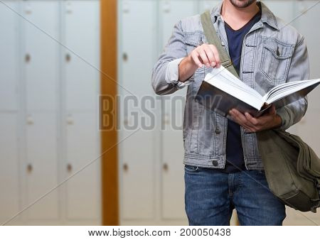 Digital composite of male student holding book in front of lockers