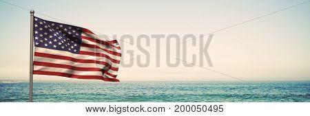 Digital composite of 3D USA flag against beach background