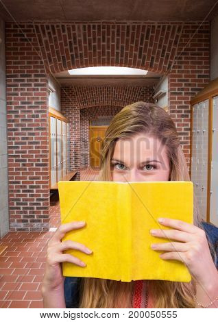 Digital composite of female student holding book in front of lockers corridor