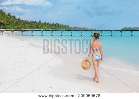 Beautiful young woman on sea beach at tropical resort