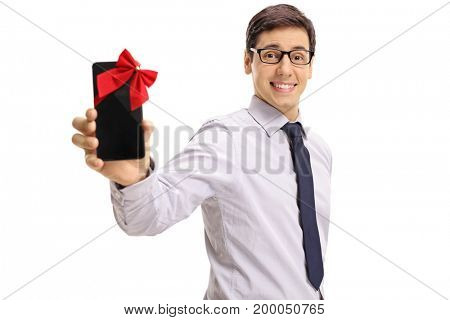 Formally dressed guy showing a phone wrapped with red ribbon as a gift isolated on white background