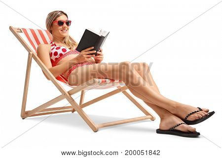 Young woman reading a book in a deck chair isolated on white background