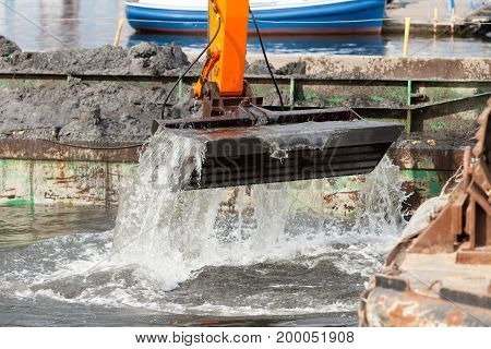Excavator shovel digging in sand from water. Building construction industrial objects concept.