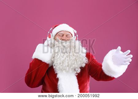 Santa Claus listening to music on color background