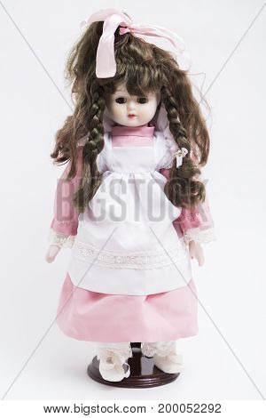 Portrait of ceramic porcelain handmade vintage brunette doll with two pigtails in old pink textile silk dress and white apron with embroidery, bow on head and white boots on white background.