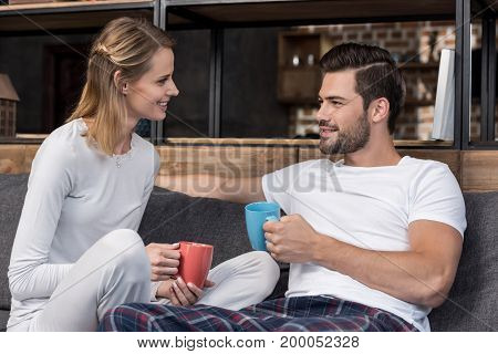 happy young couple with coffee cups looking at each other
