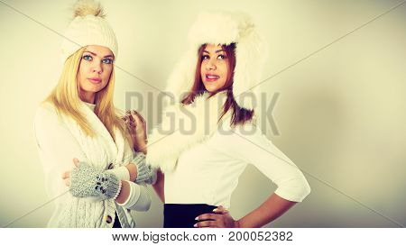 Clothing people fashion concept. Two ladies in winter outfit. Blonde woman together with mulatto girl wearing white warm clothes.