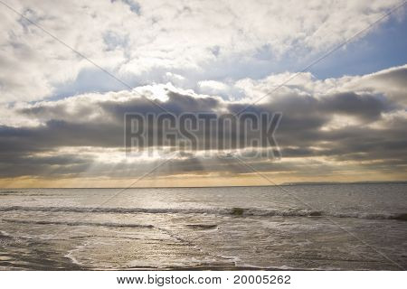 Beautiful Inspirational Sunset Over English Coastal Landscape With Sun Bemsn Penetrating Moody Cloud