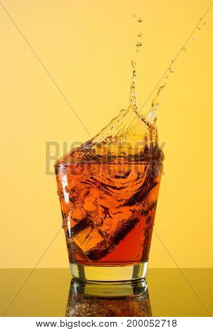 Whiskey splashes out of glass on yellow background.