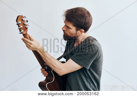 A man with a beard on a light background holds a guitar, tuning, music, musical instruments.