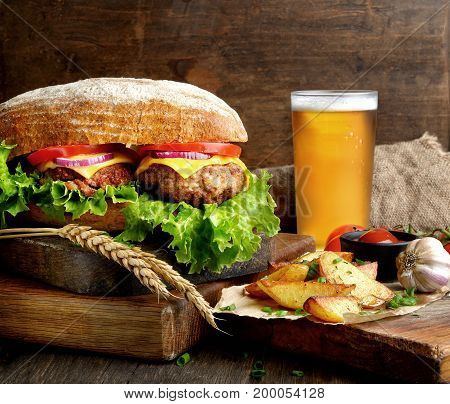 Big and tasty hamburger on desk with beer  and fried potatoes on dark background