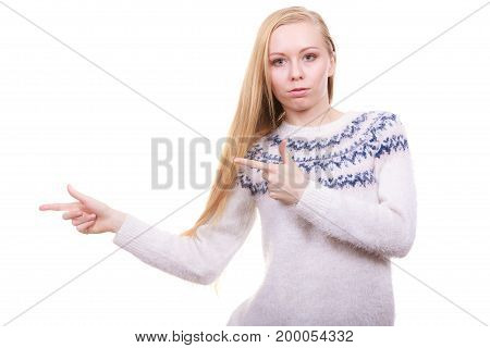 Paying attention to something advertisement concept. Teenage blonde woman in winter furry jumper and black trousers pointing at blank copyspace.