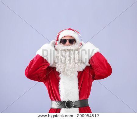 Santa Claus listening to music on light background