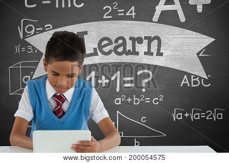 Digital composite of Student boy at table using a tablet against green blackboard with learn text and education and schoo