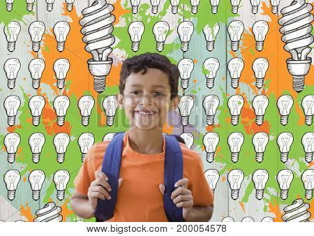 Digital composite of Schoolboy in front of light bulb graphics and orange and green paint
