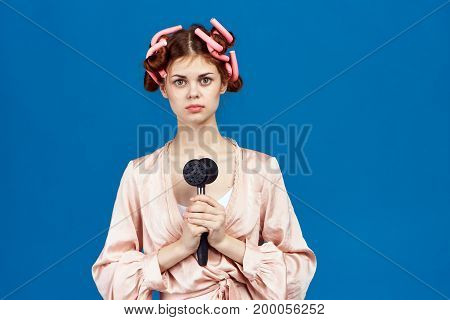 Beautiful woman housewife on a blue background holds a hammer for beating meat, cooking, curlers, blank space for copying.