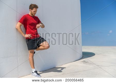 Smartwatch runner man checking progress on smart fitness sport watch during running break cardio workout training. Athlete relaxing using online app on wearable device. Outdoor active lifestyle.