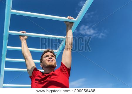 Fitness monkey bars man training arms muscles on jungle gym outdoors in summer. Athlete working out gripping climbing on ladder equipment at sport athletics centre.