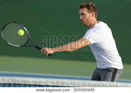 Tennis player hitting ball with backhand racket on hard court. Man playing game returning ball portrait.