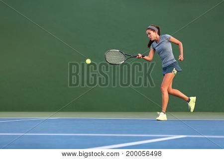 Tennis player Asian woman playing with racket hitting ball with forehand on outdoor court. Asian girl athlete training on green copy space background.