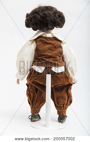 Ceramic porcelain handmade vintage doll of brunette boy with curly hair in in old brown crumpled velour masquerade costume with vest and elegant shirt with embroidery on white background.