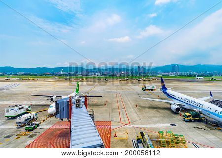 TAIPEI TAIWAN - JUNE 09: This is a view of the runway of Songshan airport with airplanes getting ready to board passengers on June 09 2017 in Taipei