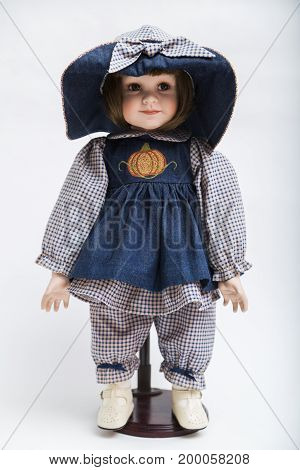 Portrait of ceramic porcelain handmade vintage smiling positive brunette doll in old blue denim dress with orange pumpkin embroidery, big hat, bow, plaid shirt, pants and boots on white background.