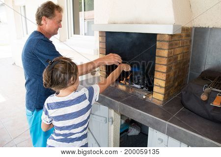 grandfather makes a barbecue with his granddaughter for family holidays