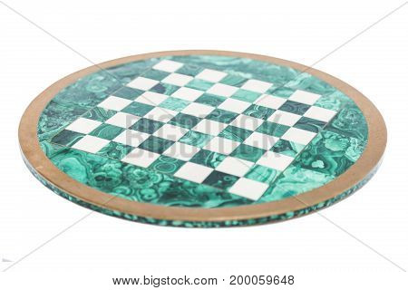 Shiny round green stone empty vintage old chess board from above with golden yellow frame on isolated white background.