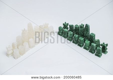 Shiny green and white transparent stone vintage old handmade chess pieces on white background.