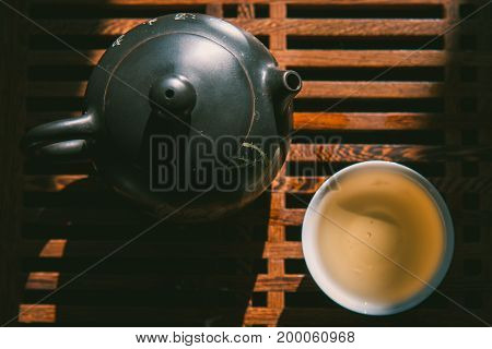 Chinese tea ceremony. Top view tea set: teapot and a cup of green puer tea on wooden table. Asian traditional culture
