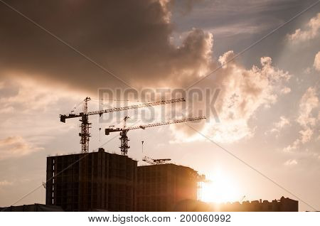 Construction site at sunset. tower cranes against the sky. building under construction