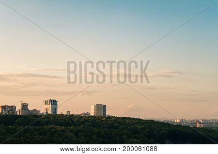 High-rise buildings and a hill with trees, a city among the trees, preserving the environment in the capital