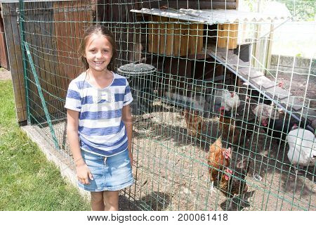 Girl Child In The Summer With A Chicken Coop In The Garden
