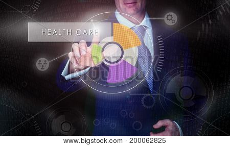 A Businessman Selecting A Health Care Button On A Computerised Display Screen.