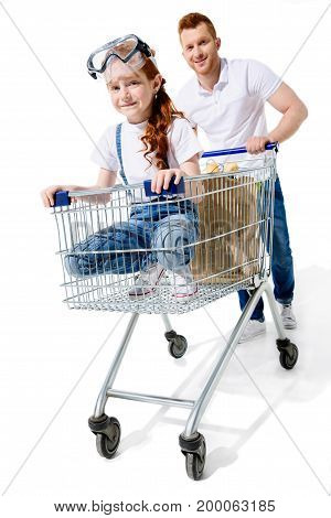 happy young father carrying cute little daughter in shopping cart isolated on white