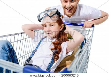 happy father carrying shopping cart with cute little daughter sitting inside isolated on white