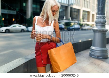 Photo of woman with packages near city buildings during day