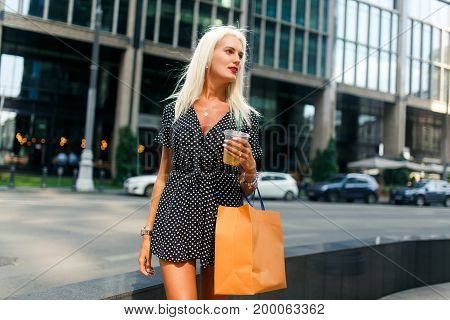 Photo of woman on shopping trip with packages near buildings in city during day