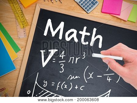 Digital composite of Math equations written on blackboard with chalk in hand
