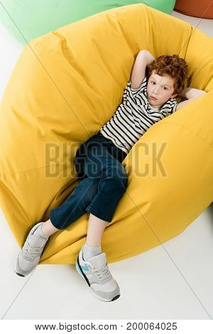 high angle view of cute redhead boy lying on bean bag chair and looking at camera